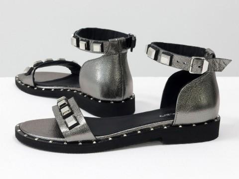 Босоножки на низком ходу цвета никель из кожи с металлической фурнитурой и шипами по периметру