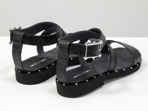 Черные босоножки из кожи питон украшены металлическими шипами по периметру